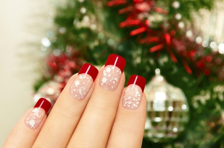 Winter manicure with red lacquer and white chips on the background of the Christmas tree.